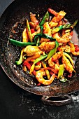 A wok with fillet of sole, prawns and sweet-and-sour vegetables