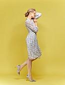 Blonde Frau in gemustertem Sommerkleid und Pumps mit Blumenstickerei