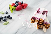 Yogurt, berry and granola breakfast popsicles on marble surface