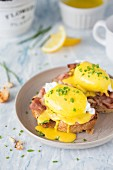 Eggs Benedict (poached eggs with crispy bacon and hollandaise sauce) on a toasted bread