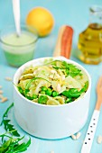 Farfalle pasta with creamy sauce, peas, rocket, lemon and pine nuts