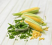 Petit pois and corn on the cob on a wooden background