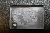 An icing sugar snowflake on a baking tray (seen from above)