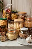 Vorratsgläser mit Nudeln, Nüssen, Marmelade, Oliven, Obst und Linsen auf Marmorplatte