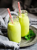 Vegan green smoothies in glass bottles with straws