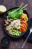A buddha bowl with quinoa, lentils, sweet potato, edamame, tofu, spinach and hummus