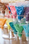 Verschiedenfarbige Zuckerdekore in Spritzbeuteln auf Ständern