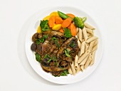 Mushroom ragu with penne and vegetables on a plate in front of a white background (seen from above)