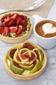 A fig tart, a strawberry tart with pistachios, and a cappuccino