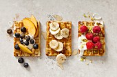 Belgian waffles with three different toppings (seen from above)