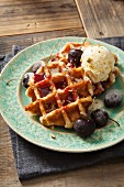 Round Belgian waffles with cherries, cherry sauce and vanilla ice cream