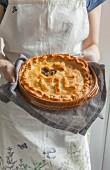Frau hält Fleischpie verziert mit Schriftzug Pie und Teigherz