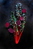 Red chard and beetroot halves in front of a black background