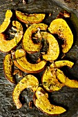 Grilled pumpkin slices with olive oil, garlic and thyme on an oven tray