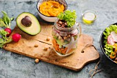 Mixed salad in a glass jar with sweet potato puree