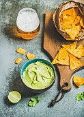 Mexican corn chips, fresh guacamole sauce and glass of beer on wooden serving board over grey concrete table background, selective focus, vertical composition