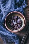 Schälchen mit Bitterschokolade in Stückchen gebrochen (Aufsicht)