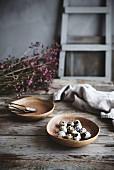 Stillleben mit Wachteleiern und Blütenzweigen auf rustikalem Holztisch in Landhausküche