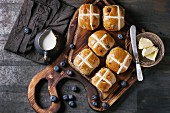 Hot cross buns on wooden cutting board served with butter, knife, fresh blueberries and jug of cream