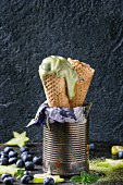 Waffle cones of Green tea matcha soft elastic ice cream with mint leaves, carambola, lime, blueberries in old tin can