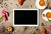 Tablet, coffee and croissants on grey stone background