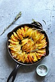 Crispy leaf potato roast on a frying pan, seasoned with salt and black pepper