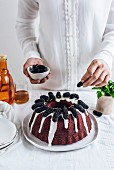 A woman with white shirt topping a red velvet bundt cake with black mulberries