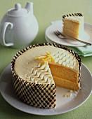 A sliced sponge cake with a decorative border