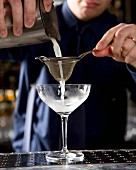 A person pouring a cocktail from a shaker through a strainer into a glass