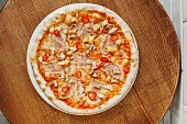 Pizza with ham, pineapple and chillies on a wooden board (top view)