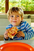 Playful Caucasian boy eating slice of pizza