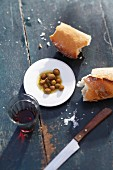 Olives with bread and a glass of red wine on a rustic wooden table