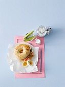 A sesame bagel with smoked salmon, dill, horseradish cream cheese, a hard-boiled egg and sour milk with herbs and cucumber