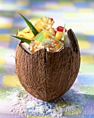 Rice pudding with candied fruits in a coconut husk