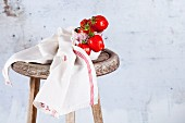 Small plum tomatoes on a wooden stool with a tea towel