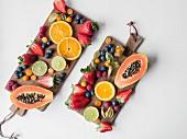 Frische Früchte auf zwei Holzbrettern angerichtet (Aufsicht)