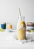 Mango and pineapple smoothie served in a glass bottle with a straw