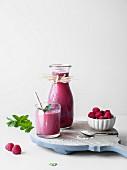 Pinkfarbener Lakritz-Himbeersmoothie serviert in Glas und Karaffe
