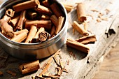 Cinnamon sticks inside and next to a tin on a wooden surface