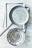 Kitchen utensils for different cooking methods: a pan, a baking tray and a steamer basket