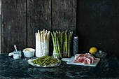 Various types of asparagus, ham, a lemon and salt