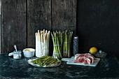 Various types of asparagus, ham, a lemon and salt