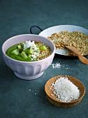 Green smoothie bowl with kiwi, matcha powder, nuts and buckwheat