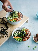 Colourful salmon sushi bowl with nori and edamame