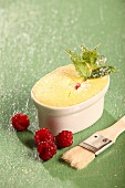A small cheesecake in an ovenproof dish with raspberries and mint leaves
