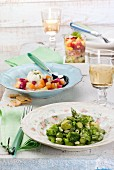 Green vegetable salad with asparagus, potato salad with tuna and egg and seafood salad