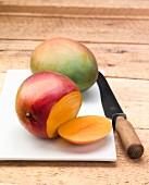 One whole and one sliced mango