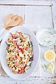 Colourful vegetable salad with yoghurt and dill dressing and lemon
