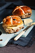 Hot cross buns with butter on a wooden chopping board (Easter baking, England)