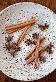Star anise and cinnamon sticks on a plate